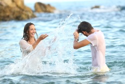 Spontaneous couple joking throwing water bathing in the sea on the beach