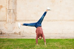 Spontaneous young woman in city park holiday, doing cartwheel on grass in front of stone wall texture building, outdoors. Teenager celebrating dynamic energy fun, travel recreation leisure lifestyle.