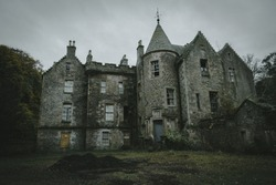 Spooky abandoned castle in Scotland nestled in the green winter foliage. The castles steeples are set against a sombre grey sky background. The scene is eerie creepy lonely and cold.