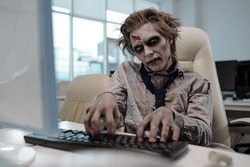 Spooky businessman with zombie body painting looking at computer screen and typing