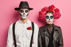 Spooky couple wear skull makeup and prepares for all soul day or halloween dressed in costumes isolated on pink background. Underworld creatures indoor ready for religious ritual or festival