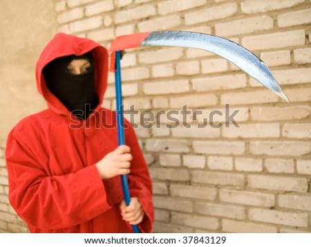 Spooky figure in red hood holding a sharp scythe. Focus is on a scythe but person is out of fucus