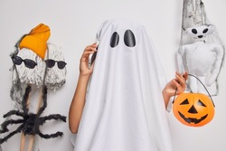 Spooky ghost holds carved orange pumpkin calls friends via smartphone invites for halloween party poses around creepy creatures isolated over white background. Horrible night on 31st of October