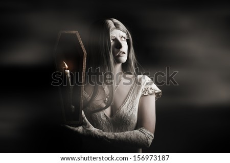 Spooky gothic girl walking through a haunted horror house with candle coffin during a chilling ghost tale