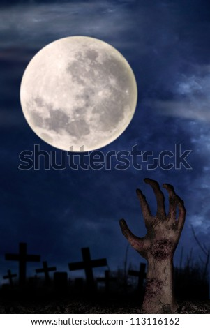 Spooky graveyard with zombie hand coming out of the ground