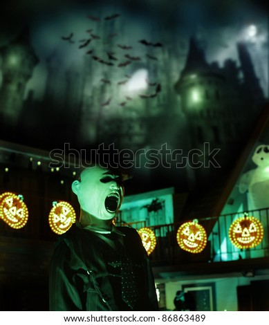 Spooky Halloween concept image of scary castle and bats in background with glowing pumpkins and monster in foreground