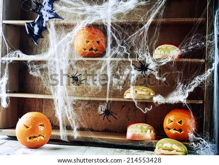 Spooky Halloween pantry with pumpkin lanterns and apples shaped as open mouths with teeth on wooden shelves draped in spider webs crawling with large black spiders