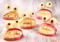 Spooky Halloween party favors or decorations made from fresh apples and dough in the form of open mouths lined with teeth topped with round googly eyes on a rustic table, creative country handicraft