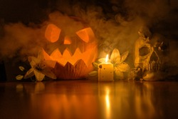 spooky halloween pumpkin in darkness as the smoke passes by