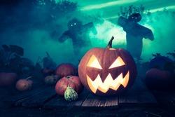 Spooky Halloween pumpkin on dark field with scarecrows
