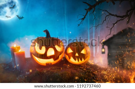 Spooky halloween pumpkins in dark mistery forest. Scary halloween background with free space for text. #1192737460