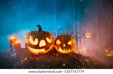 Spooky halloween pumpkins in forest. Scary halloween background with free space for text. #1187767774