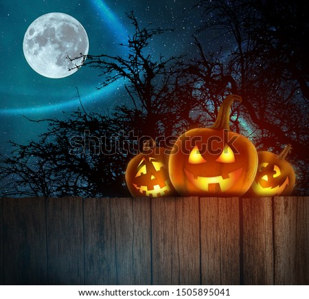 Spooky Halloween Pumpkins on wood. Halloween Background At Night Forest with Moon.