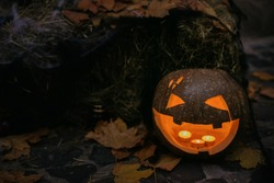 Spooky Jack-o'-lantern with glowing faces and cobweb in dark. Pumpkin with scary carved face on hay with candle light, modern festive halloween street decor. Happy Halloween