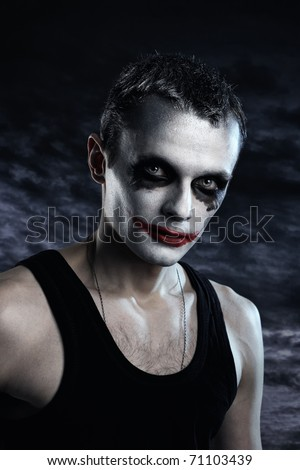 Spooky man joker on dark background