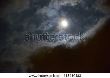 Spooky Moon shines through clouds. Halloween background.
