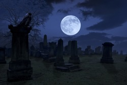 Spooky night at cemetery with old gravestones, full moon and black raven. Horrible Halloween night photograph