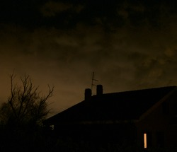 Spooky night: dark sihouettes of a house and a bare tree with dark clouds in the background