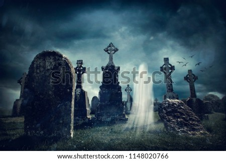 Spooky old graveyard and a ghost at night