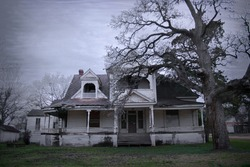 Spooky old haunted house with a dead tree in the yard in rural Texas.