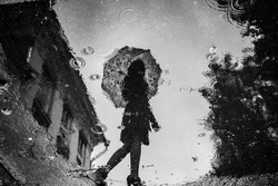 Spooky puddle reflection of girl with umbrella shadow