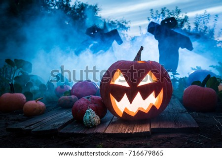 Spooky pumpkin with scarecrows on the field for Halloween #716679865