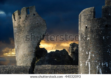 Spooky ruined castle lit by sunset and bright moonlight