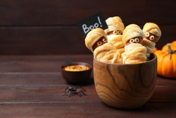 Spooky sausage mummies for Halloween party served on wooden table, space for text