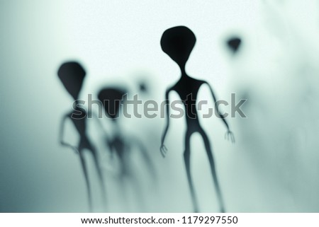 Spooky silhouettes of aliens and bright light in background. 3D rendered illustration.