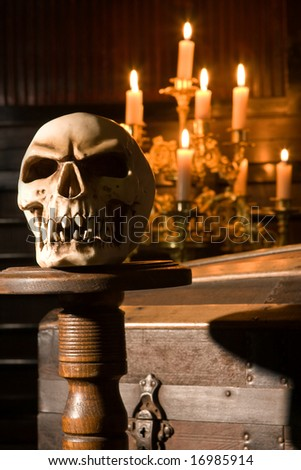 Spooky skull lit by candles in gothic surroundings