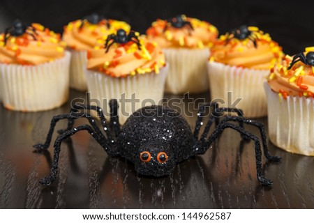 Spooky spider with orange and yellow Halloween cupcakes