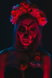 Spooky young female with skeleton makeup wearing floral wreath under bright and red illumination during Halloween party in dark room