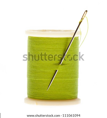 Spool of thread and needle on a white background