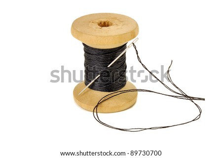 spool of thread with a needle closeup on white background