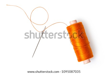 spool of thread with a needle on white isolated background