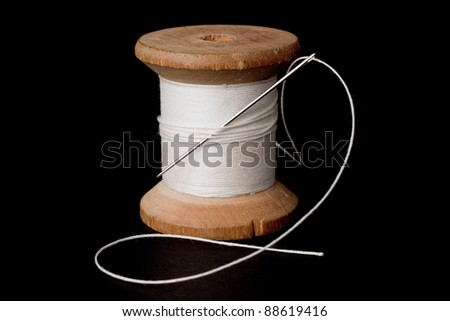 Spool of white thread and a needle over a black background
