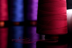 Spools of colored cotton thread, ordered composition, warm colors, red spool in the foreground with the red wire coiled in the form of  black table reflection, sprockets into the background blurred