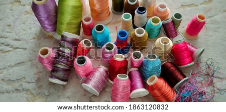 Spools of colored plastic threads, scattered threads on the floor Stok fotoğraf ©