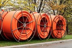 Spools of orange fiber optic conduit on a mobile reel for fiber optic cable installation