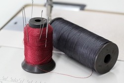 Spools of sewing thread on the table. A red spool in the form of a needle holder.