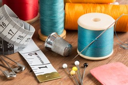 Spools of thread and basic sewing tools including pins, needle, a thimble, and tape measure on a wooden tabletop