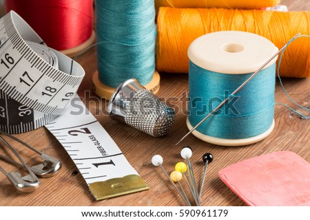 Spools of thread and basic sewing tools including pins, needle, a thimble, and tape measure on a wooden tabletop #590961179