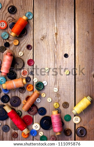 Spools of threads and buttons on old wooden table