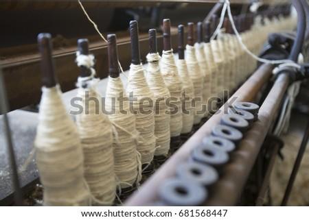 spools of white wool yarn on...