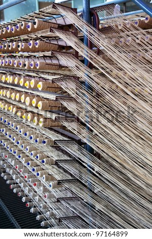 spools with wool threads on the loom