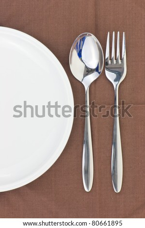 Spoon and fork on a napkin as a dining room serving.