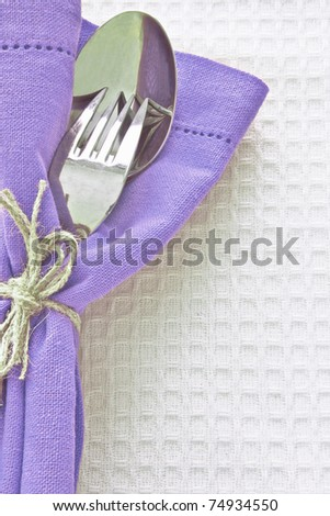 Spoon and fork with colorful serviette on white linen cloth