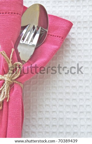 Spoon and fork with pink serviette on white linen cloth