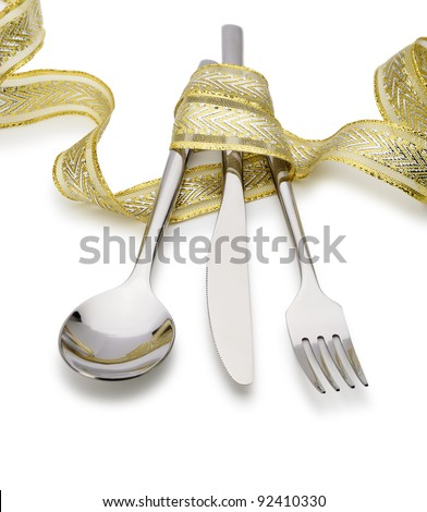 Spoon, fork and a knife tied up celebratory ribbon. It is isolated on a white background