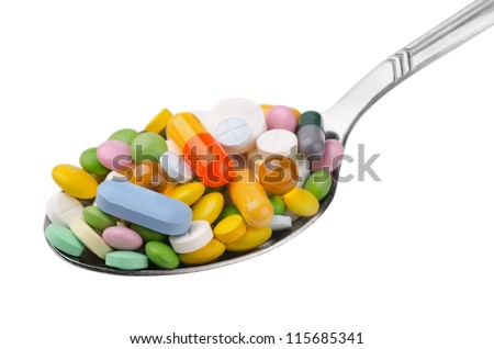 Spoon full of various colorful drugs isolated on white